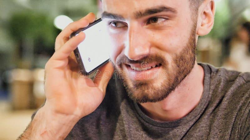 Jeune homme dehors au callig de nuit sur le téléphone portable photo stock