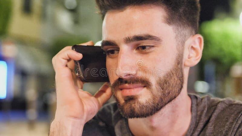 Jeune homme dehors au callig de nuit sur le téléphone portable images stock