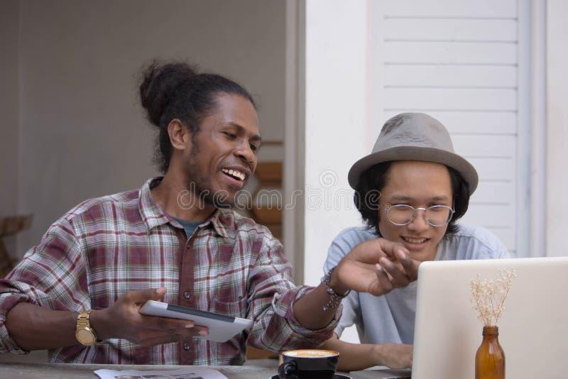 Jeune homme deux créatif discuter avec l'ordinateur portable et le comprimé, le jeune Asiatique et l'homme de couleur travaillant photographie stock libre de droits