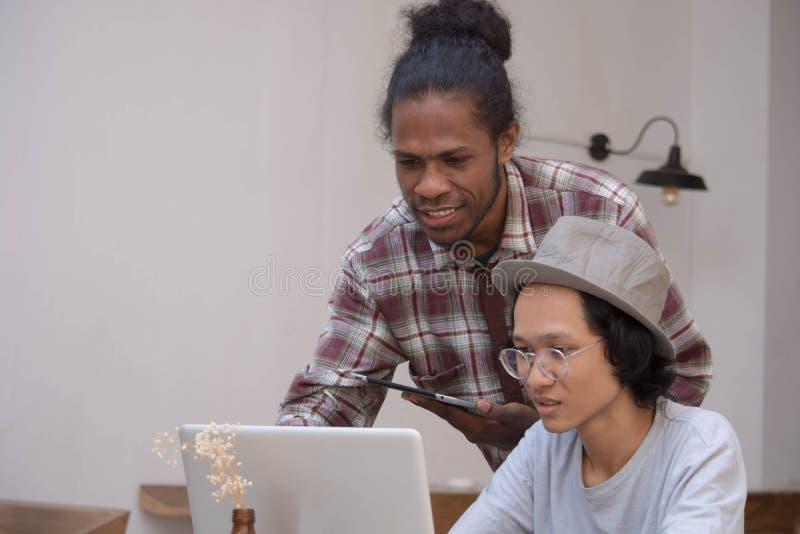 Jeune homme deux créatif discuter avec l'ordinateur portable et le comprimé, le jeune Asiatique et l'homme de couleur travaillant image stock