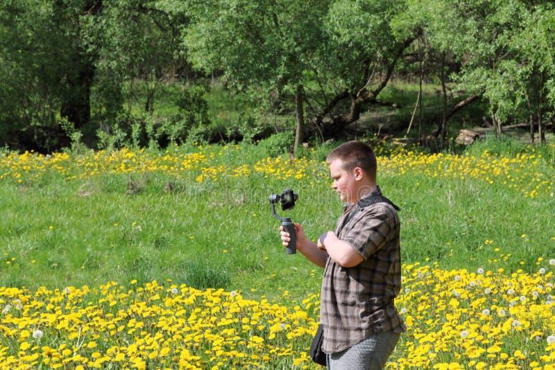 Jeune homme dodu dans un pr? avec les pissenlits de floraison Conduit l'enregistrement vid?o sur un smartphone install? sur un ca photos libres de droits