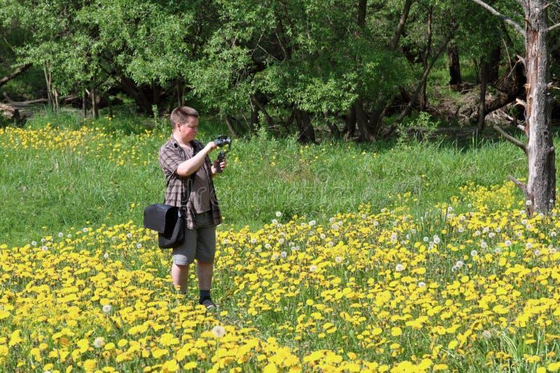 Jeune homme dodu dans un pr? avec les pissenlits de floraison Conduit l'enregistrement vid?o sur un smartphone install? sur un ca photo libre de droits