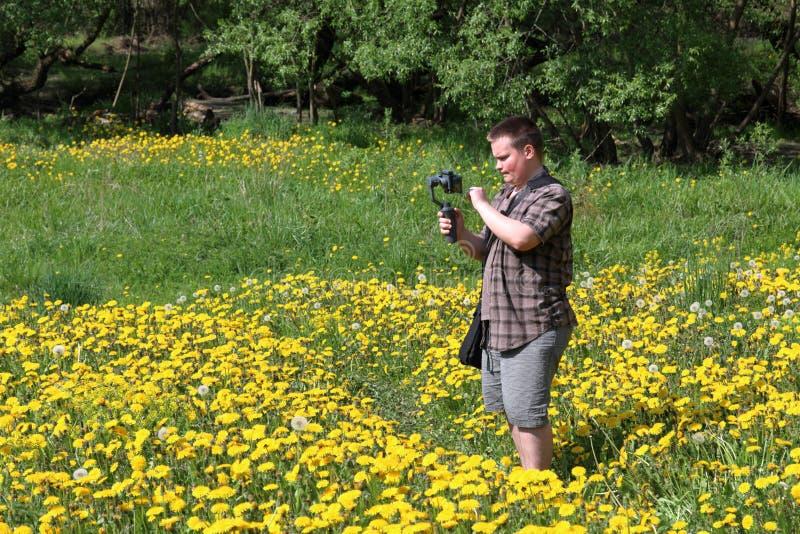 Jeune homme dodu dans un pr? avec les pissenlits de floraison Conduit l'enregistrement vid?o sur un smartphone install? sur un ca photos stock