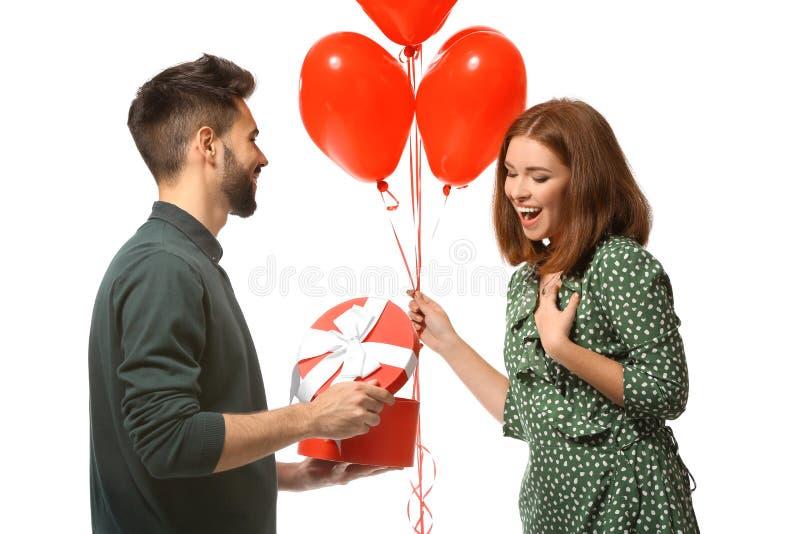 Jeune homme donnant le présent à son amie aimée sur le fond blanc Célébration de Saint-Valentin de saint photos stock