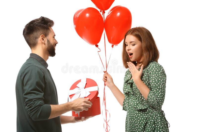Jeune homme donnant le présent à son amie aimée sur le fond blanc Célébration de Saint-Valentin de saint images libres de droits