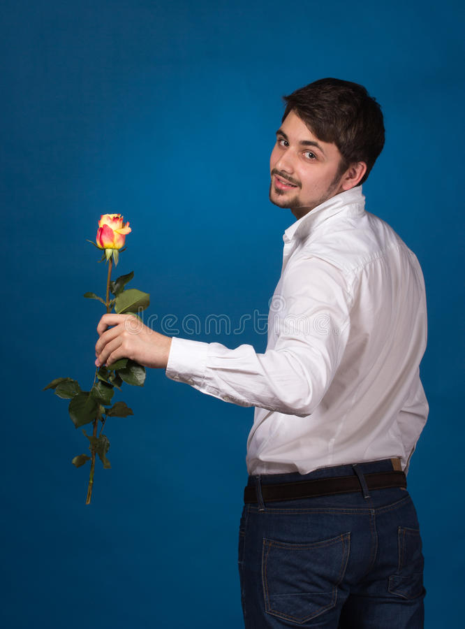 Jeune homme donnant une rose rouge photographie stock