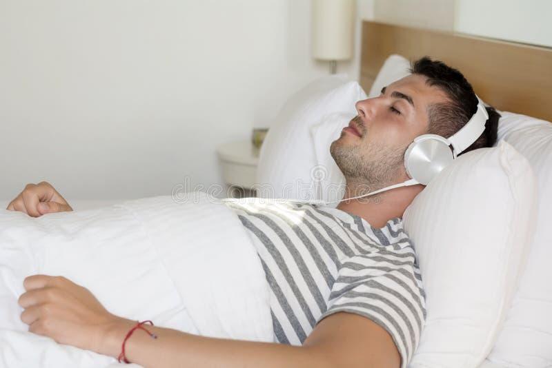 Jeune homme dormant dans la musique de écoute de lit photos stock