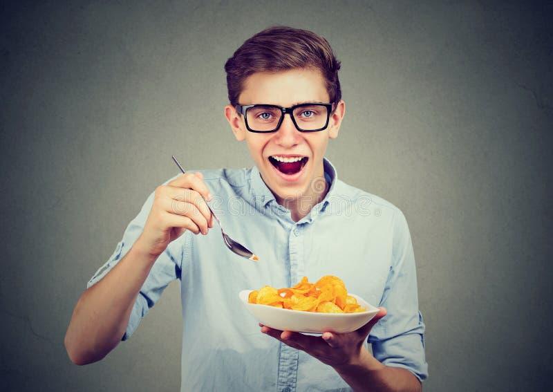 Jeune homme drôle ayant un plat des pommes chips images libres de droits