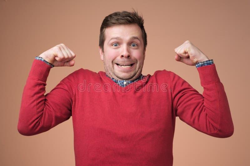 Jeune homme drôle dans le chandail rouge, biceps d'expositions au-dessus du fond blanc image stock