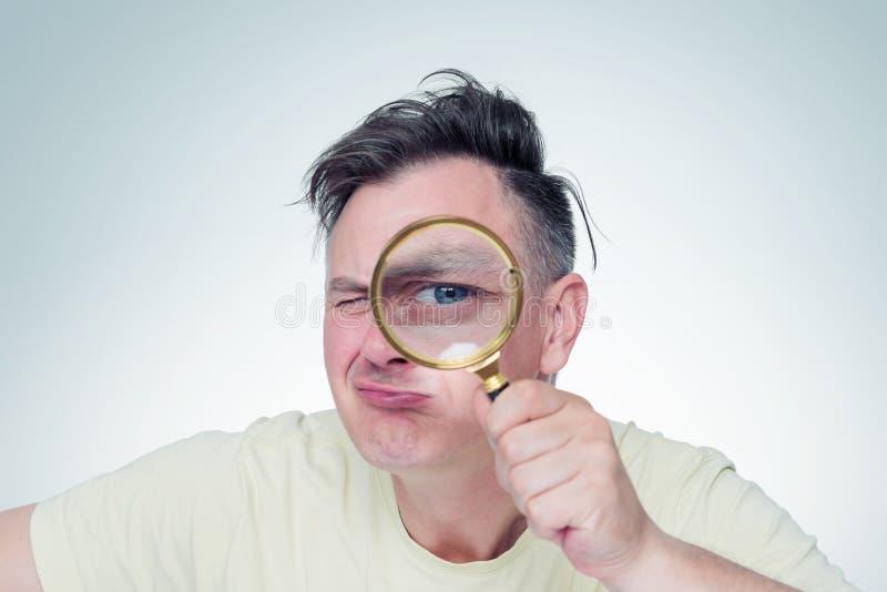 Jeune homme drôle regardant par la loupe, sur le fond clair images stock