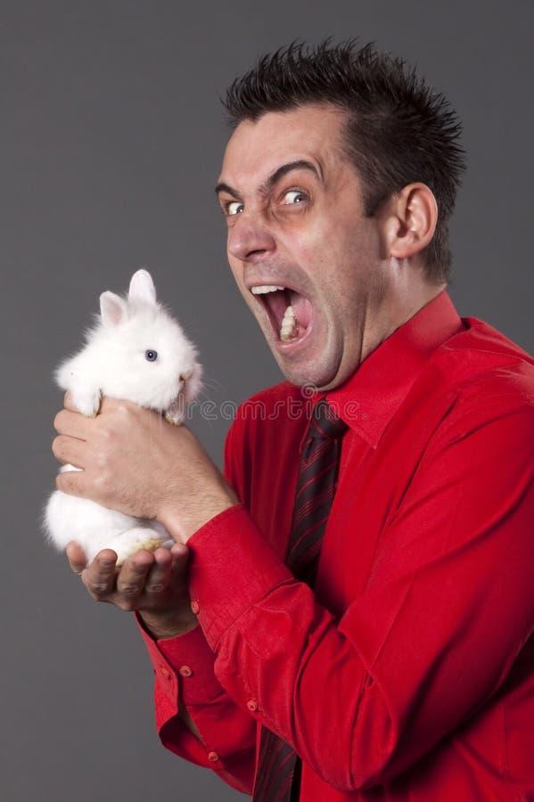 Jeune homme drôle retenant le lapin blanc photo stock