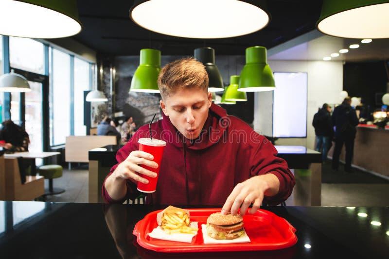 Jeune homme drôle s'asseyant dans un restaurant de prêt-à-manger, tenant un verre de boisson et prenant un hamburger du plateau photographie stock libre de droits
