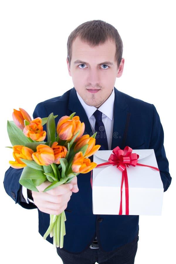 Jeune homme drôle avec le groupe de fleurs et de boîte-cadeau d'isolement sur W photos stock