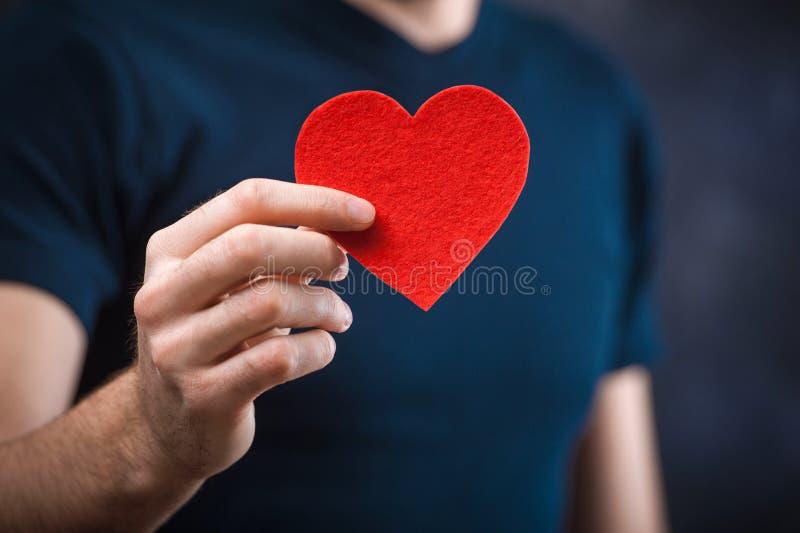 Jeune homme drôle avec tenir le coeur rouge pour les vacances photographie stock libre de droits