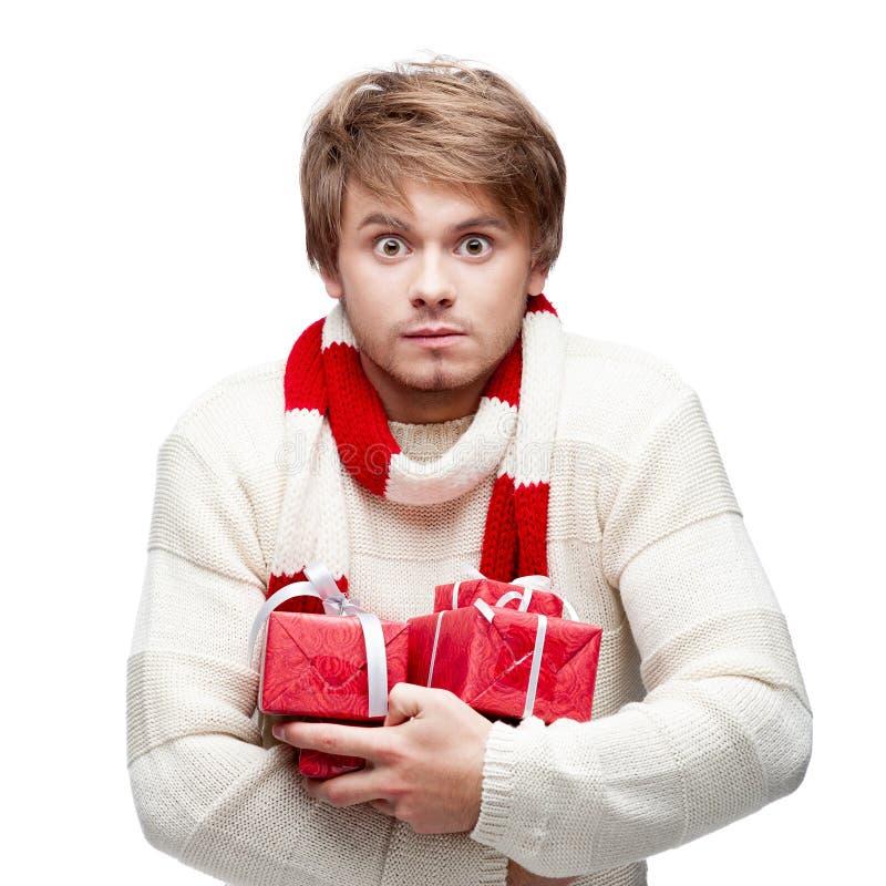 Jeune homme drôle tenant des cadeaux de Noël photographie stock