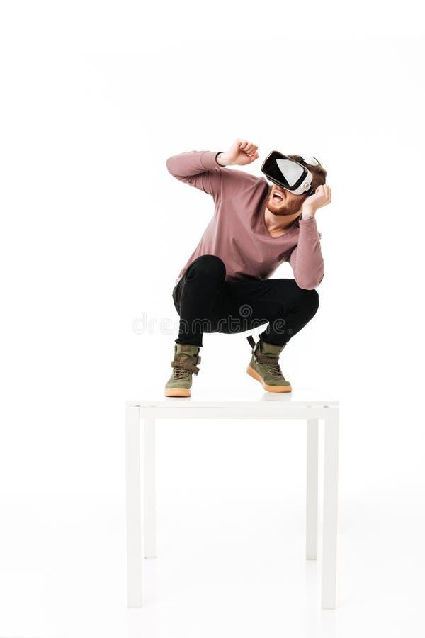 Jeune homme effrayé se tenant sur la table blanche dans la couverture de studio et de prise de quelque chose tout en jouant avec  photo stock