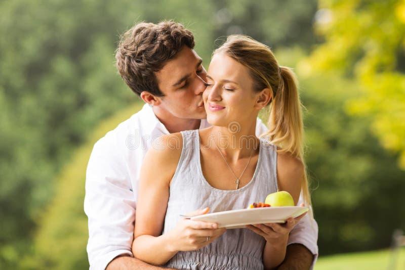 Jeune homme embrassant l'amie photographie stock libre de droits