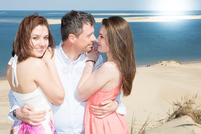 Jeune homme embrassant une femme et tenant des autres par le bord de mer photo libre de droits
