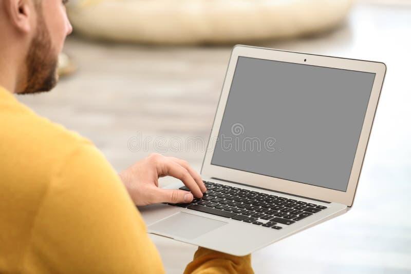 Jeune homme employant la causerie visuelle sur l'ordinateur portable ? la maison L'espace pour la conception photo libre de droits