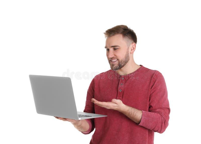 Jeune homme employant la causerie visuelle sur l'ordinateur portable contre le blanc photo stock