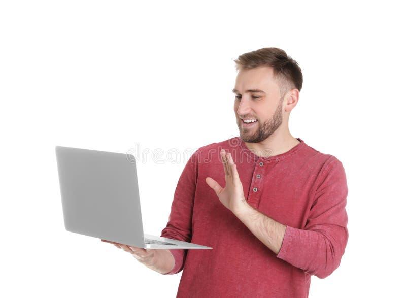 Jeune homme employant la causerie visuelle sur l'ordinateur portable photos stock