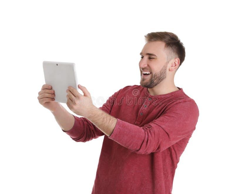 Jeune homme employant la causerie visuelle sur le comprim? contre le blanc photo libre de droits