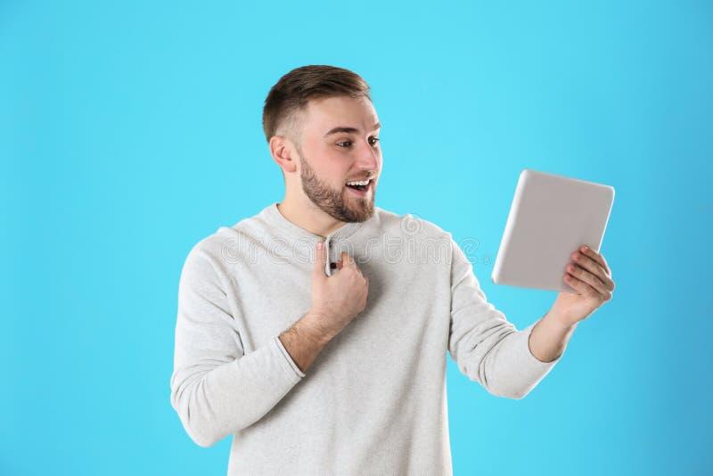 Jeune homme employant la causerie visuelle sur le comprim? image stock