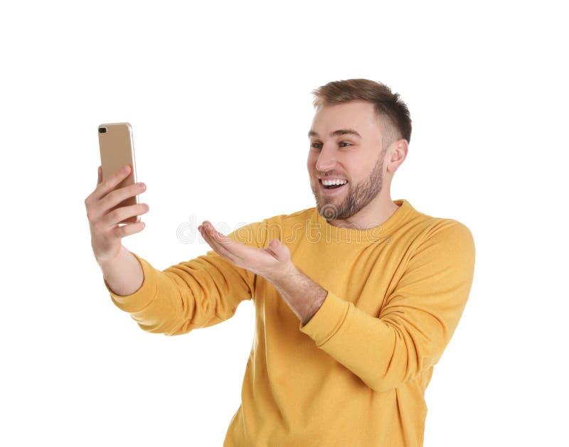 Jeune homme employant la causerie visuelle sur le smartphone contre le blanc photographie stock libre de droits