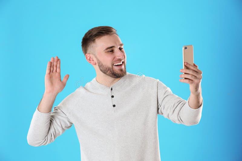 Jeune homme employant la causerie visuelle sur le smartphone images libres de droits
