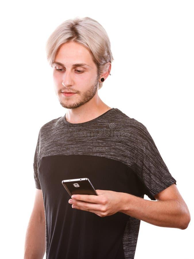 Jeune homme employant le service de mini-messages de téléphone portable sur le smartphone photos libres de droits