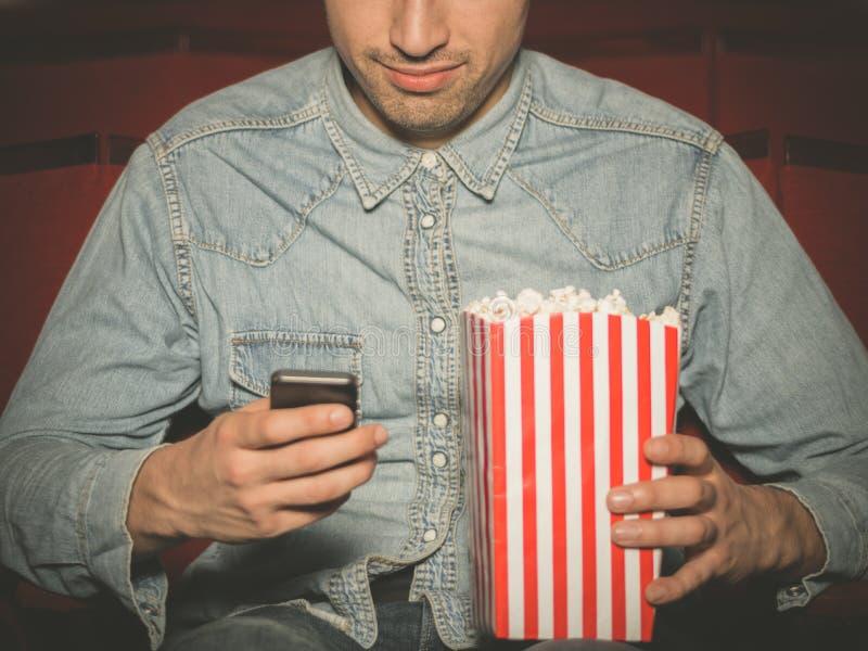 Jeune homme employant le sien téléphone au cinéma photographie stock
