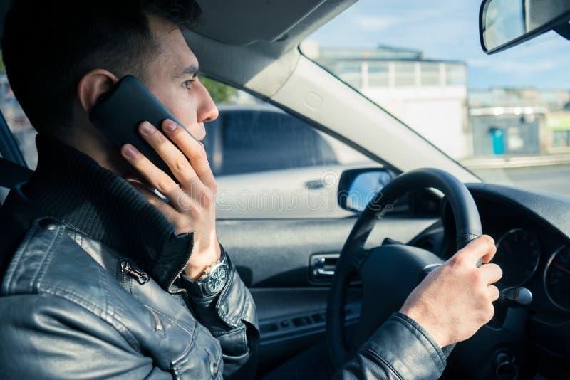 Jeune homme employant le sien téléphone tout en conduisant la voiture Piloter dangereux images stock