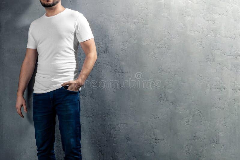 Jeune homme en bonne santé avec le T-shirt blanc sur le fond concret avec le copyspace pour votre texte photos libres de droits
