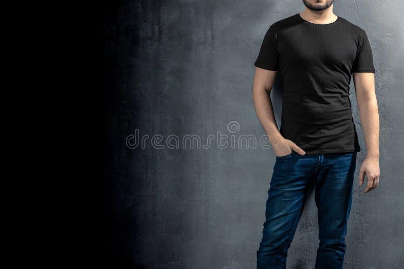 Jeune homme en bonne santé avec le T-shirt noir sur le fond concret avec le copyspace pour votre texte image libre de droits