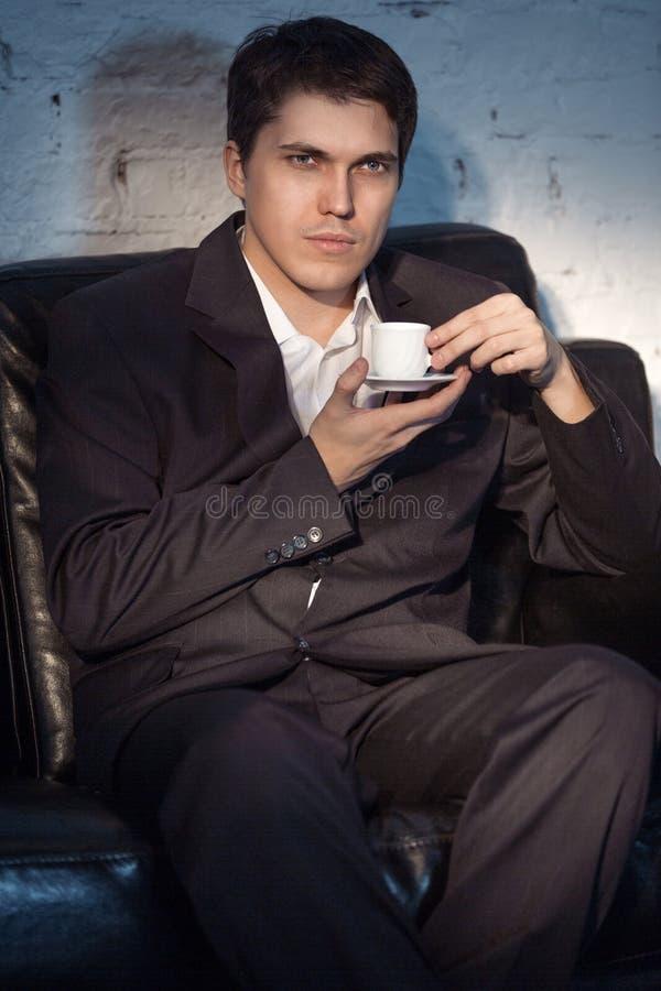 Jeune homme en café de boissons de costume image stock