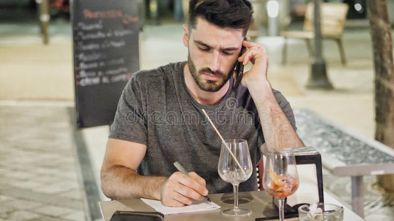 Jeune homme en dehors de callig sur le téléphone et l'écriture photographie stock libre de droits
