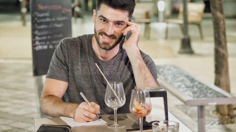 Jeune homme en dehors de callig sur le téléphone et l'écriture photos libres de droits