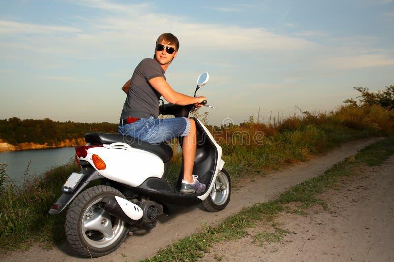 Jeune homme en glaces pour conduire un scooter photographie stock libre de droits