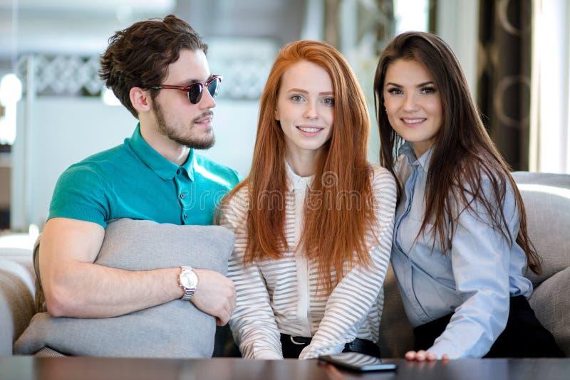 Jeune homme en verres avec le cusion dans des mains regardant deux femmes belles photographie stock