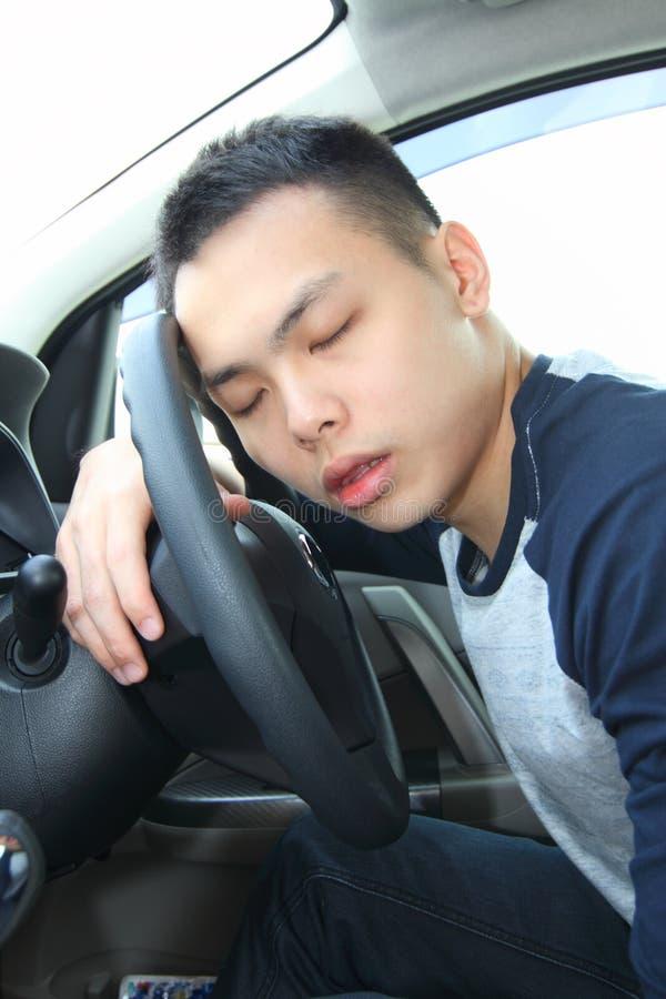 Jeune homme endormi à la roue photos stock