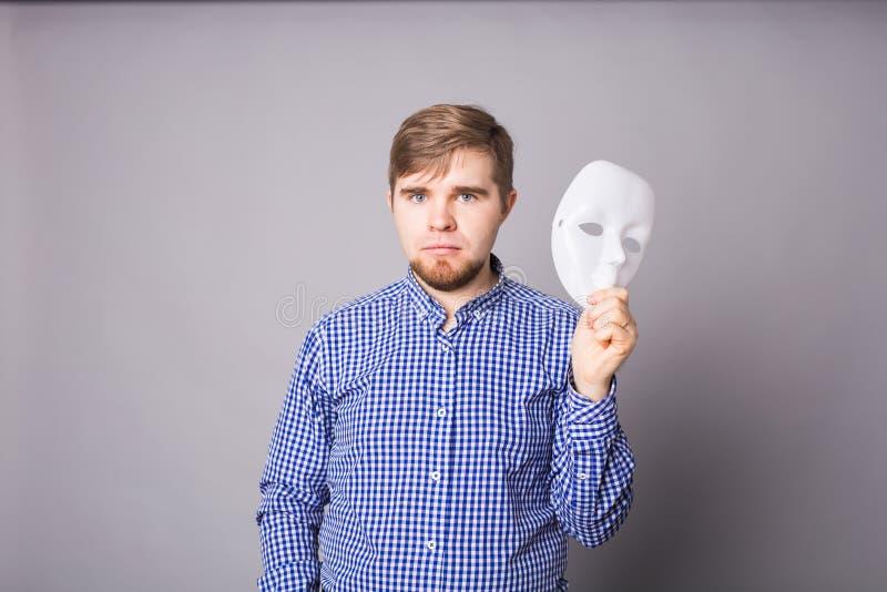 Jeune homme enlevant le visage de indication de masque blanc simple, fond gris image libre de droits