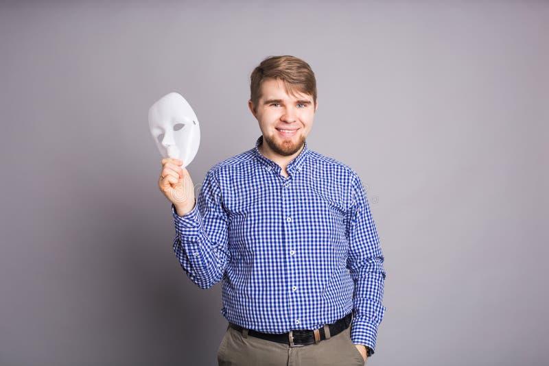 Jeune homme enlevant le visage de indication de masque blanc simple, fond gris photo libre de droits