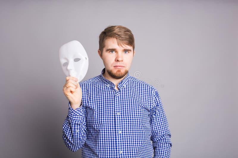 Jeune homme enlevant le visage de indication de masque blanc simple, fond gris photographie stock libre de droits