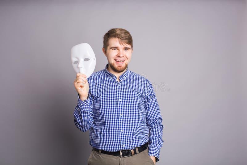 Jeune homme enlevant le visage de indication de masque blanc simple, fond gris images libres de droits