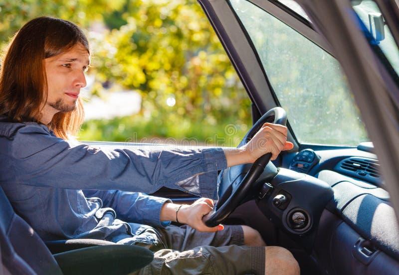 Jeune homme ennuy? avec de longs cheveux conduisant la voiture photographie stock