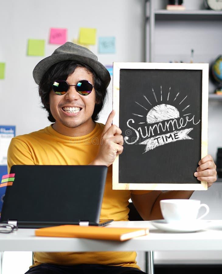 Jeune homme enthousiaste tenant la typographie d'heure d'été sur le tableau noir W image stock