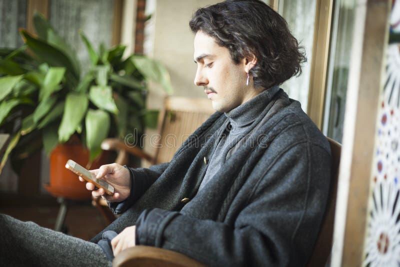 Jeune homme espagnol à l'aide du smartphone se reposant sur une terrasse images stock