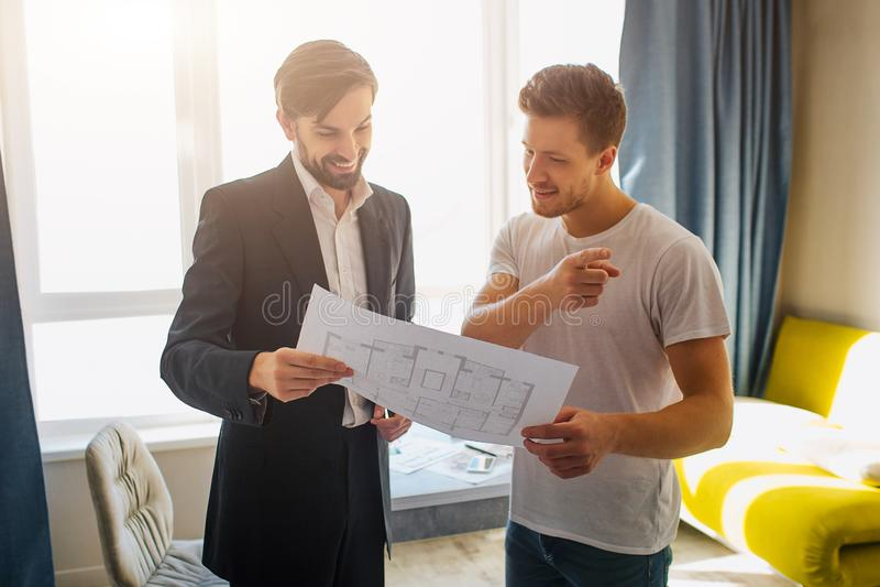 Jeune homme et appartement d'achat ou de loyer d'agent immobilier Le client et l'agent immobilier beaux concentrés ont l'affaire  images stock