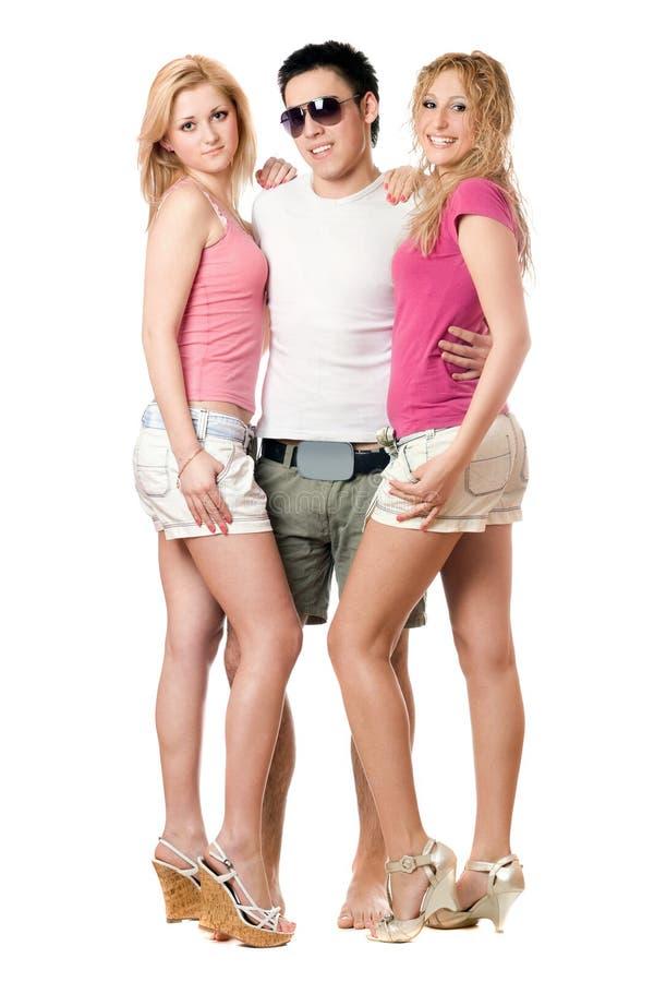 Jeune homme et deux belles filles photo stock