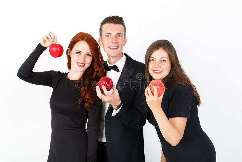 Jeune homme et deux femmes dans le noir sur un fond blanc photos stock